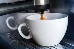 White ceramic cups in the coffee machine Royalty Free Stock Photo