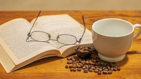 White ceramic empty cup surrounded by small spread of roasted coffee beans, with eye glasses and book atop a wooden coffee table royalty free stock image