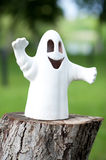 White ceramic ghost on a stump in the park Royalty Free Stock Photo