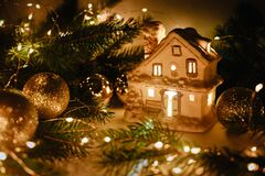 Free White Ceramic House, Shiny Balls And Christmas Tree Branches With Golden Bokeh Of Garland. Magic Wallpaper. Christmas Candlestick Stock Image - 203950551