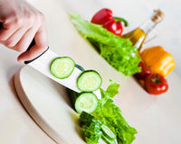 White ceramic knife cucumber chopping Royalty Free Stock Photos