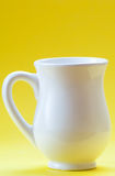 White ceramic milk jug on  yellow background Stock Photos