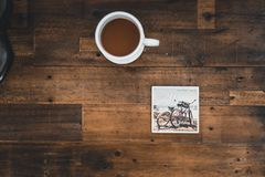 White Ceramic Mug With Coffee Beside Photo of Two Mountain Bikes Royalty Free Stock Images