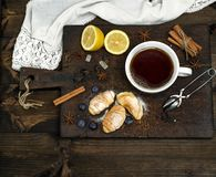 White ceramic mug with hot black tea. Next baked croissants and lemon, top view Royalty Free Stock Images