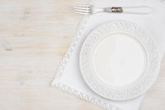 White ceramic plate with fork over placemat on wooden table. Background Stock Photography