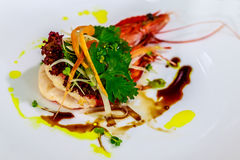 White ceramic plate with jumbo prawn herb salad with lettuce, parsley, carrot stripes and bean sprouts with balsamic reduction. S. Ide view Stock Photo