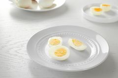White ceramic plate with sliced hard boiled eggs wooden table. Nutrition concept. White ceramic plate with sliced hard boiled eggs on wooden table. Nutrition royalty free stock image