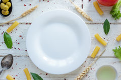 White ceramic plate surrounded by italian tortiglioni pasta, bay leaves and other ingredients. Royalty Free Stock Photo