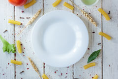 White ceramic plate surrounded by italian tortiglioni pasta, bay leaves and other ingredients. Royalty Free Stock Image