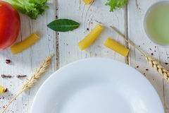 White ceramic plate surrounded by italian tortiglioni pasta, bay leaves and other ingredients. Stock Photo