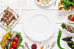 White ceramic plate surrounded by snacks, void Royalty Free Stock Images