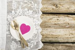 White ceramic plates on a simple wooden background with a white vintage lacy tablecloth with silverware table Stock Photo