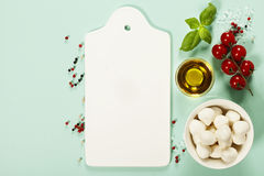 White ceramic serving board and salad ingredients over light blu Stock Photography