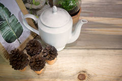 White ceramic tea jar. On plantation table with rustic looks with pine cone and picture frame decorated Stock Image