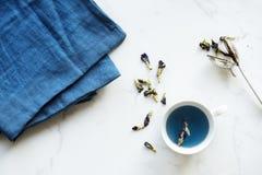 White Ceramic Teacup Near Blue Textile Stock Photos