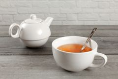 White ceramic teapot and cup of hot amber tea on gray wood desk. royalty free stock photography
