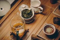 White Ceramic Teapot Beside Cup With Leaves Stock Images