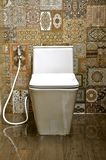 White ceramic toilet in a tiled room stock images