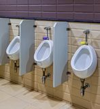 White Ceramic Urinals for Men in Public Toilet Room Royalty Free Stock Image