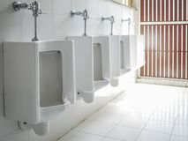 white ceramic urinals for men public toilet stock images
