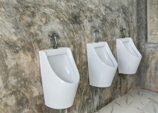 White ceramic urinals for men on raw concrete wall Royalty Free Stock Photo