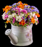 White ceramic watercan, sprinkler, with vivid colored flowers, orange tagetes, purple wild flowers, close up Royalty Free Stock Photography