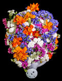 White ceramic watercan, sprinkler, with vivid colored flowers, orange tagetes, purple wild flowers, close up Stock Photo