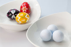 White ceramics bowls, golf balls and eggs Stock Photos