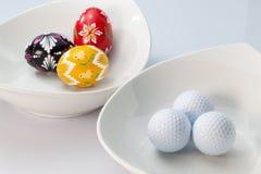White ceramics bowls, golf balls and eggs stock photos