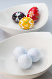 White ceramics bowls, golf balls and eggs Royalty Free Stock Photo