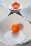 White ceramics bowls and orange golf ball. Four white ceramics bowls and golf ball Stock Images