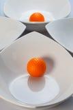 White ceramics bowls and orange golf ball. Four white ceramics bowls and golf ball Royalty Free Stock Images