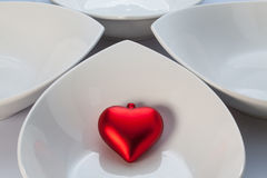 White ceramics bowls and red heart Stock Photography