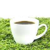 White ceramics cup on artificial grass Stock Images