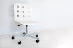 White chair against wall Stock Photos