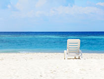 White chair on the beach stock images