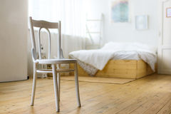 White chair in the bedroom. Bed and paintings on the wall Stock Photography