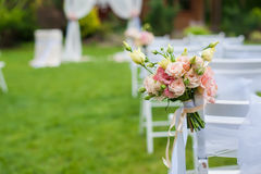 White chair with a bunch of flowers. White chair standing on a green glade, prepared for the wedding ceremony. The chair is decorated with a bouquet of flowers Stock Photography