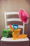 White chair with child's play items for day at the beach Royalty Free Stock Image