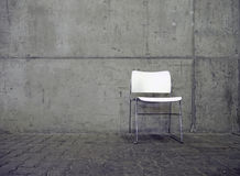 White chair and concrete wall Stock Photos