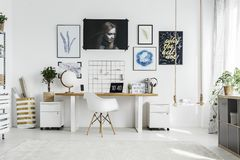 White chair in home office. White chair at wooden desk in bright home office interior with posters and plant on cabinet royalty free stock photo