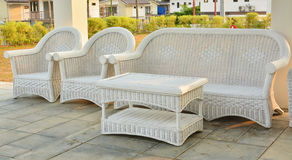 White chair made of rattan. White chair and small table made of rattan Royalty Free Stock Photos