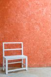 White chair and orange wall Royalty Free Stock Photos