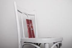 White chair with red gift and silver angel ribbon Stock Images