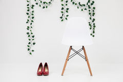 White chair with red shoes on a white background Stock Photos