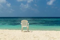 White chair on white sand of  tropical beach against the turquoise water of the Indian Ocean, Maldives Stock Image