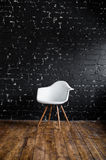 White chair standing in room on brown wooden floor over black brick wall Royalty Free Stock Images