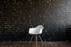 White chair standing in room on brown wooden floor over black brick wall Stock Photo