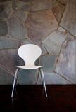 White Chair by stone Wall. A white chair by a natural stone wall Stock Photos