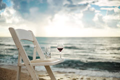 White chair with wineglass on a beach. Left after wedding banquet stock image